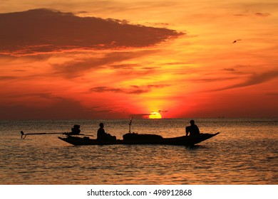 Beautiful sunrise on the beach and silhouette of fishing boat.