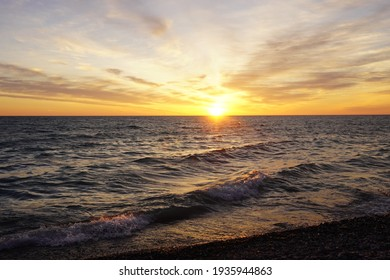 A beautiful sunrise on a lake from a rocky beach.