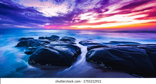 Beautiful sunrise over the beach in long exposure panaroma. Moving elements sunrise and wave photography from the rocky beach in india. , slow-shutter Sea Waves and Rocks photography.