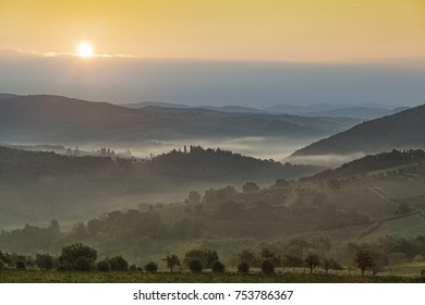 Beautiful sunrise over Castellina in Chianti with some fog between the hills with vineyards in Tuscany in Italy
