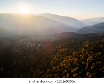 Beautiful sunrise over the colorful autumn forest. October Forest.Foggy mountain. Beautiful sunset over the valley wit colorful forest in autumn season. Scenic sunset over the forest hills. Autumn