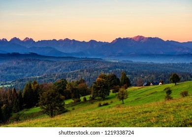 Beautiful sunrise over green meadows and settlement in front of high rocky peaks in High Tatras mountains in a background on Slovak and Polish border.