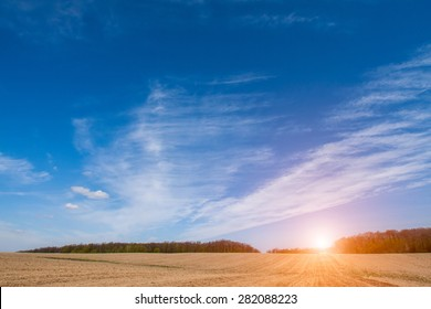 Beautiful sunrise over the large brown field in spring season