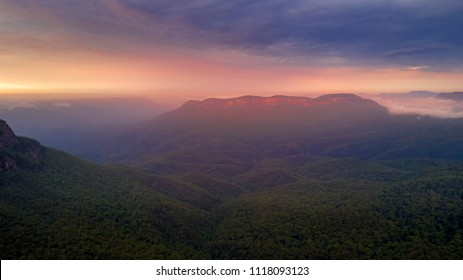 Beautiful sunrise over mist-filled Jamison Valley. In the distance Mt Solitary cliffs catch the warm light. Blue Mountains Australia