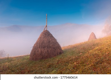 Beautiful sunrise over mountain foggy hills. Scenic landscape with sun, rising over Carpathian mountains. Haystack on grassland hill on foreground.