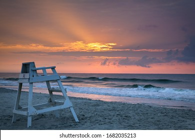 A beautiful sunrise over Myrtle beach with a lifeguard chair on the shore in South Carolina