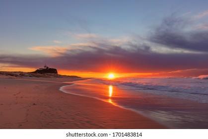 Beautiful sunrise over Nobbys Beach. Nobbys Lighthouse  in the distance.Newcastle,Hunter Region of N.S.W. Australia.