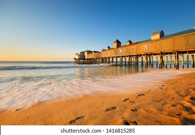 Beautiful sunrise over Old Orchard Beach Pier, Saco Maine USA. The wooden pier on the beach contains many other tourist businesses, including a variety of souvenir shops.