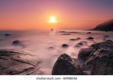 a beautiful sunrise over the rocky coast with the sun over the horizon