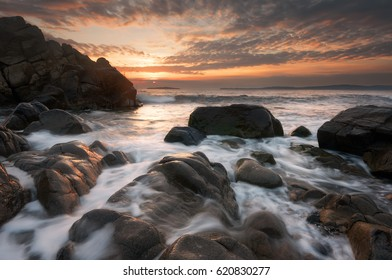 Beautiful sunrise over the sea. Cloudy dramatic sky, big waves. Magnificent cloudscape near the shore.