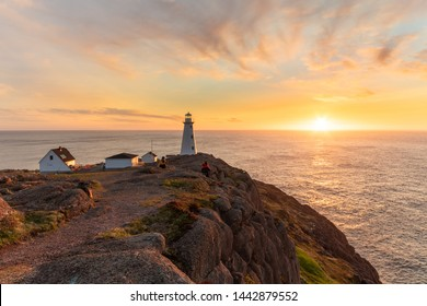 Beautiful sunrise over a white lighthouse sitting at the edge of a rocky cliff. Cape Spear National Historic Site, St Johns Newfoundland.