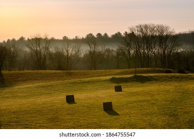 A beautiful sunrise picture of a meadow with hay bales and fog in the countryside of Virginia near Shenandoah National Park.