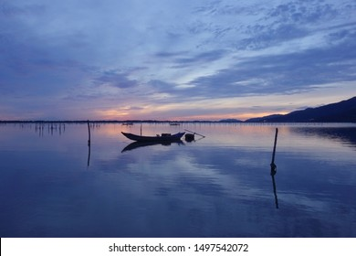 Beautiful sunrise with red purple sky & cloud over the river view and floating house with boats on the water. Natural beauty of Twilight dawn break at Lap An swamp - Danang vietnam landscape