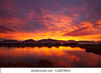 Beautiful sunrise and the reflection on Oquirrh Lake in Daybreak, South Jordan, Utah, USA. Wasatch mountains in the background.