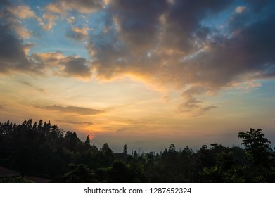 Beautiful sunrise in a rural village in Puncak, Ciloto, Cianjur, West Java, Indonesia. Silhouette of trees and rural houses.
