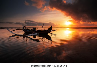"""Beautiful Sunrise Scene in Bali, Indonesia. The rowboat or """"Jukung"""" is widely use as fishing boat by the local fisherman"""