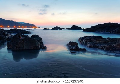 Beautiful sunrise scenery of a rocky beach in northern Taiwan, with rosy twilight glowing above the distant horizon & black rugged rocks by the coast under dramatic dawning sky (Long Exposure Effect )