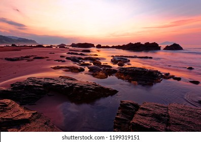 Beautiful sunrise scenery at a rocky beach in northern Taiwan, with golden sunlight reflected in the peaceful water and an island on distant horizon under dramatic dawning sky (long exposure effect)