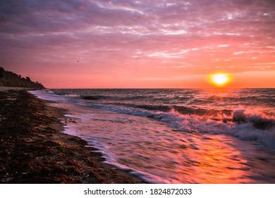 Beautiful sunrise at the sea on a cloudy morning. Ships can be seen against the background of sunrise on the horizon. Dropping off the sandy coastline. Black sea. Sanzhiika. Ukraine