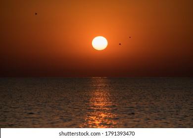 Beautiful sunrise at sea. The sun rises from the sea. The calm sea