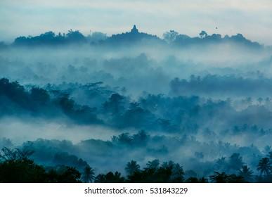 Beautiful sunrise from Setumbu Hills with a view of Mount Merapi Volcano and Borobudur Buddhist Temple (UNESCO World Heritage Site) - Java, Indonesia