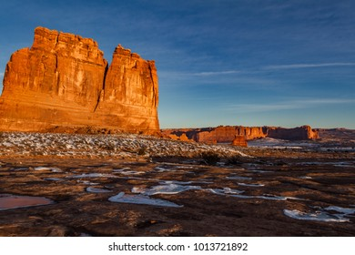 Beautiful sunrise shot of The Organ sandstone tower in Arches National Park in the winter with snow and frozen pools in Moab Utah USA.