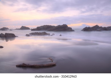 Beautiful sunrise sky over a rocky beach at Wai'ao Coast, in Yilan (Ilan) north-east to Taipei, Taiwan ~ Dramatic dawning sky reflecting on the peaceful sea water (long exposure effect)