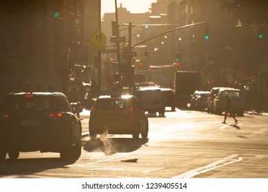 Beautiful sunrise in the streets of Manhattan with a manhole that expels steam and cars on background, New York, United States.