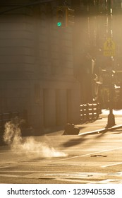 Beautiful sunrise in the streets of Manhattan with a manhole that expels steam, New York, United States.