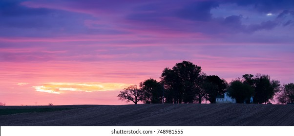 Beautiful sunrise sunset over a farm house, trees and a corn field with stubble after the harvest. Colorful rural scene in the heartland. Concepts of morning, landscape, sunrise, sunset, farming