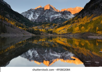 Beautiful sunrise touches Maroon bells peak at Maroon lake, Aspen, Colorado. Fall color of Aspen and reflection of the mountain