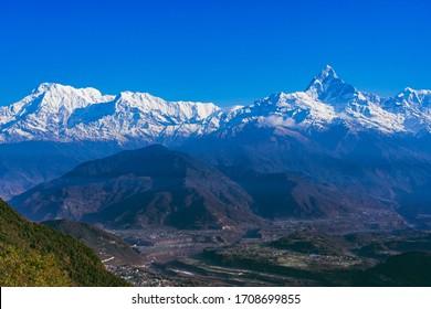 Beautiful sunrise view of mountain range with snowy peaks. Annapurna range in Himalayas. Machchapuchchre/ Fishtail, Annapurna and Himchuli Peaks, view from Sarangkot, Pokhara, Nepal.