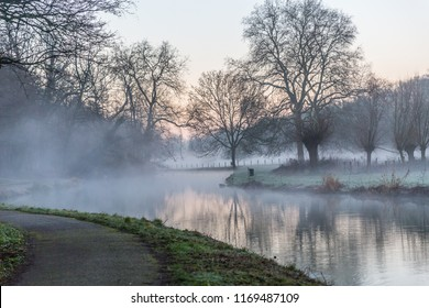 beautiful sunrise in winter in the middle of nature with a lake with haze and a path in Elsloo South Limburg in the Netherlands Holland