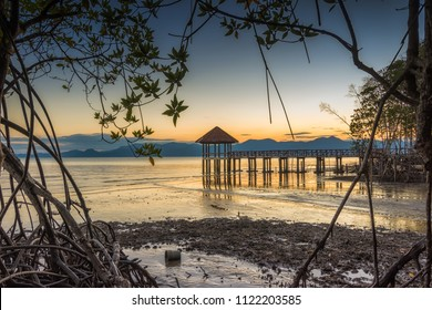 Beautiful sunrise of wooden landing with pavilion in the sea at Black Sand Beach, Trat Province of Thailand