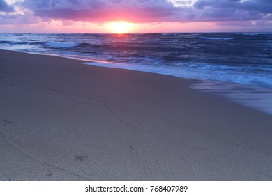 Beautiful sunrise/sunset light as waves wash up on the shore of a tropical beach