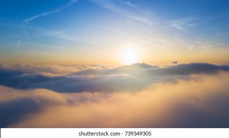 Beautiful sunset above clouds with sunrays