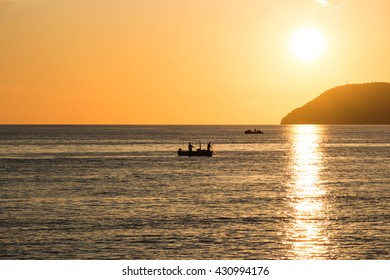 Beautiful sunset above sea with fisherman on boat