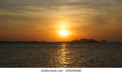 Beautiful sunset above sea or ocean. Vibrant and soft colors, magic light. Small clouds on the sky, reflection of sun in the water and sand on beach. Sea in thailand texture background