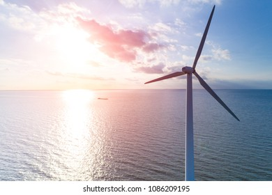 Beautiful sunset above the windmill in the ocean