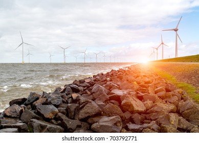 Beautiful sunset above the windmills in the ocean