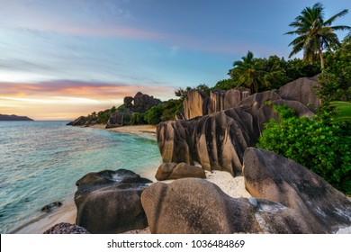 Beautiful sunset at amazing picturesque paradise beach. granite rocks,white sand,palm trees,turquoise water at tropical beach anse source d'argent, la dique, seychelles