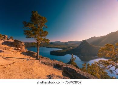 Beautiful sunset among rocky mountains and pine trees. Borovoe lake beneath. Burabay national park. Nothern Kazakhstan