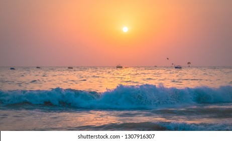 Beautiful sunset at Arabian Sea in the north Goa, India. Stunning sunset behind the sea with waves scene at the Calangute beach near Candolim in Goa, famous touristic place for summer vacations.