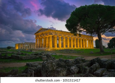 Beautiful sunset in the archaeological  site of Paestum with the temples of Neptune and Hera in the background - Campania, Italy