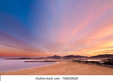 beautiful sunset in the atlantic ocean from the beach of hondarribia fuenterrabia with hendaye town in the background at the spanish french border in the basque coast