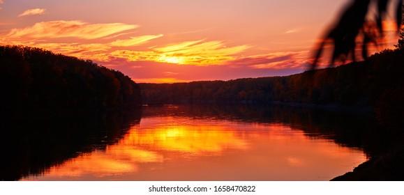 beautiful sunset in autumn season - trees silhouette near a river, bright sunlight