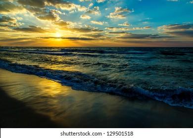 Beautiful sunset at the beach, amazing colors, light beam shining through the cloudscape over the arabian gulf seascape, united arab emirates. Dubai sea and beach