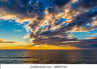 Beautiful sunset at the beach, amazing colors, light beam shining through the cloudscape over the arabian gulf seascape, united arab emirates.