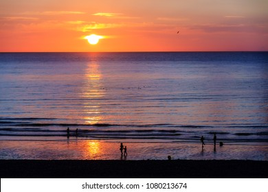 Beautiful sunset at the beach in Dieppe, Normandy, France, in summer with silhouettes in the sea