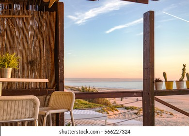 Beautiful sunset at the beach during a winter evening, seen by the beach bar made interely of wood with a very rustic aspect.